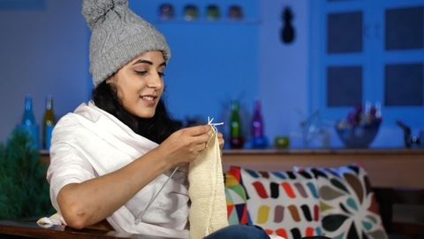 Charming Indian woman wearing a white shawl knitting sweater sitting on the sofa