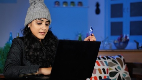 Indian woman in woolens doing online shopping - Working from home in winters