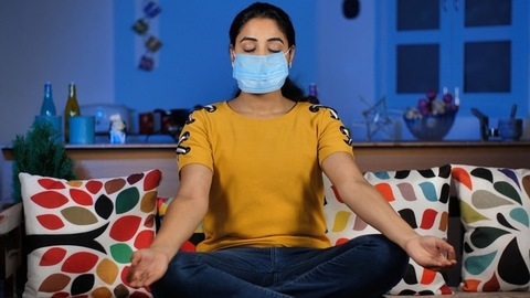 A teenager doing yoga wearing a medical mask while sitting in the lotus position