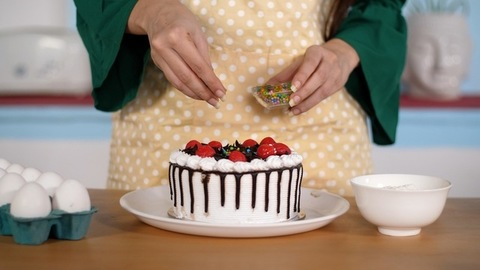 Female cook's hand sprinkling confetti sugar balls on a creamy choco-vanilla cake