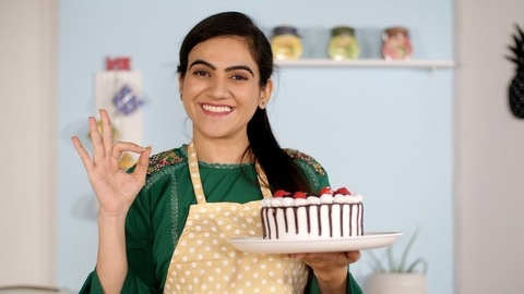 Indian home baker / food blogger with a freshly prepared cake - baking concept