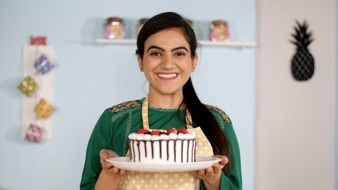 Portrait of a young Indian girl smelling the delicious aroma of a freshly-baked cake