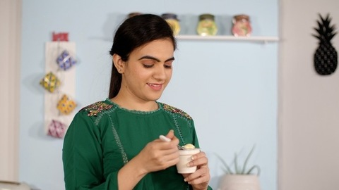 Portrait of a young Indian woman having a freshly prepared delicious dessert
