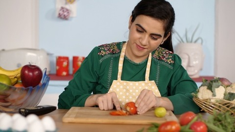 Beautiful woman preparing tasty vegetable salad sitting in the kitchen at home