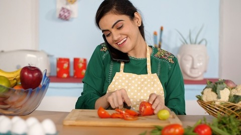 Smiling young girl receiving a phone call while chopping tomatoes in her kitchen