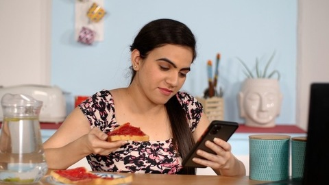 Young Indian woman having her breakfast while checking the smartphone
