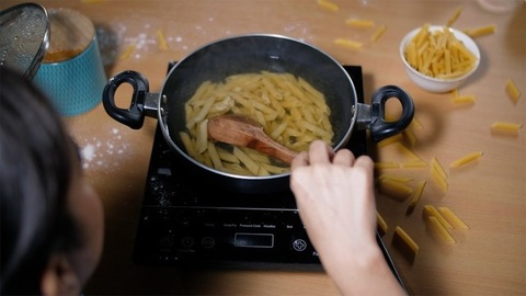 Indian woman stirring boiling penne pasta with a wooden spatula - home cooking