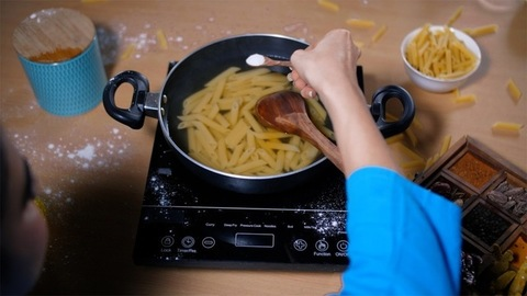 Female cook adding salt from a spice box to the boiling pasta - home-style cooking
