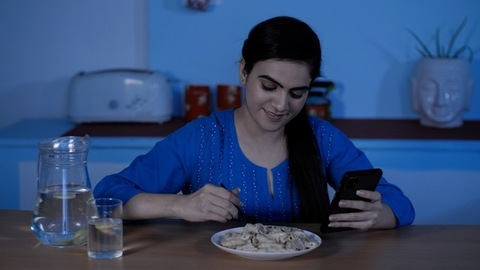 Portrait of a young woman eating snacks while browsing her smartphone
