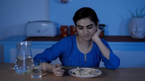Hungry-sad female feeling lonely while having dinner late at night in her kitchen