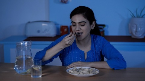 Cheerful Indian lady eating pasta / junk food in the kitchen - late-night food cravings