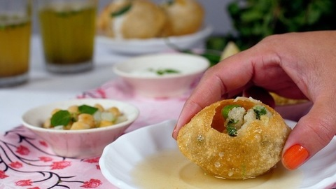 Indian woman's hand tasting / picking crunchy homemade Golgappa - tasty snacks - Street food India