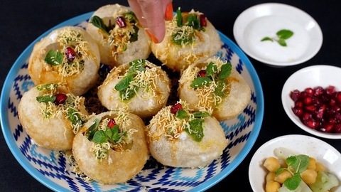 Female's hand putting Sev inside hollow puris to make a tasty evening snack - Street food India