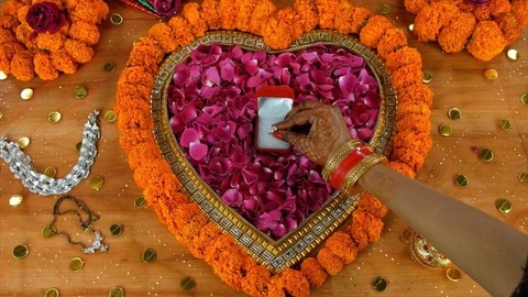 Closeup of mehndi on woman hands placing her wedding ring in a small red box