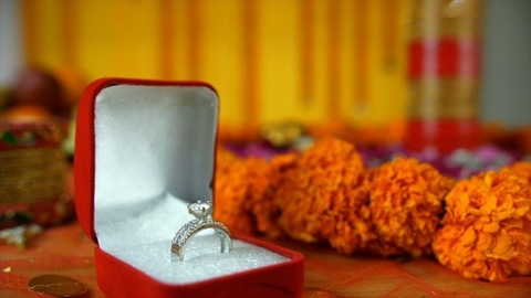 Closeup shot of Indian bride's engagement ring on a decorated floral platform