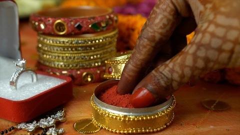 Closeup of henna mehndi on woman hands taking sindoor from a golden case