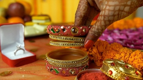 Closeup of henna mehndi on woman hands placing bangles on a decorated platform