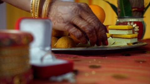 Closeup of henna mehndi on woman hands plating a tray with fresh sweets and fruits