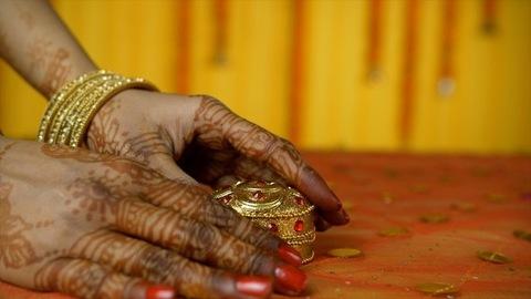 Closeup of newlywed Indian female taking sindoor from a designer sindoor box