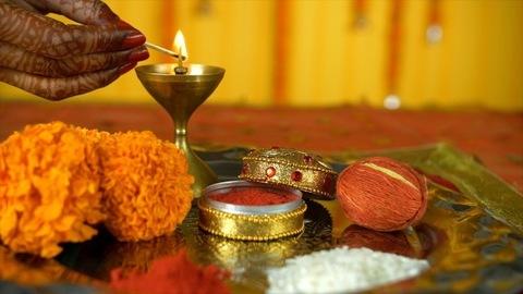 Closeup shot of mehndi on woman hands lighting up a lamp for Sindoor ceremony