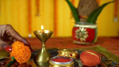 Closeup of mehndi on woman hands decorating a Puja thali for sindoor ceremony - Indian Rituals