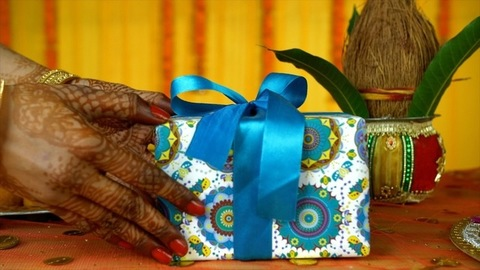 Closeup of mehndi on woman hands placing a gift box on a decorated platform - Indian Home
