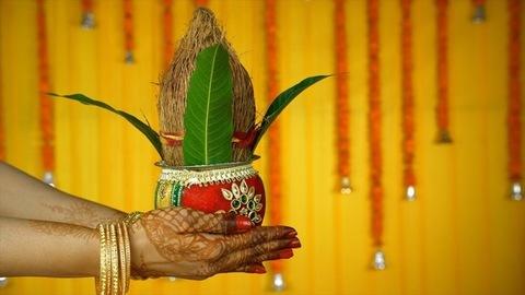 Side view shot of henna mehndi/tattoo on woman hands holding a wedding Kalash. Indian Pooja