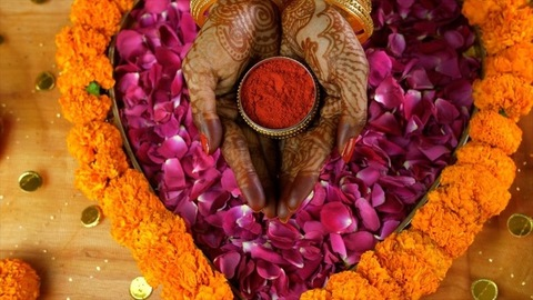 Zoom in shot of henna mehndi/tattoo on woman hands holding a sindoor box