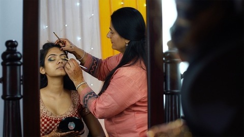 Professional make up artist doing eye makeup of a young bride on her marriage