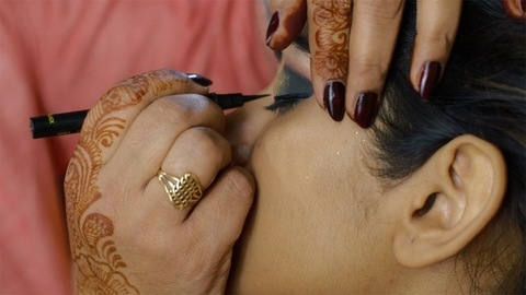 Pan shot of a female makeup artist putting black eyeliner - Indian bride makeup