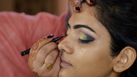 Indian bridal makeup - Beautician applying eyeliner to the upper eyelid of a girl's eyes