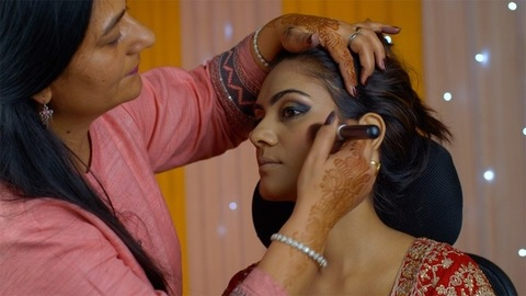 Indian bridal makeup - Professional beautician applying compact on girl's face with a soft powder brush