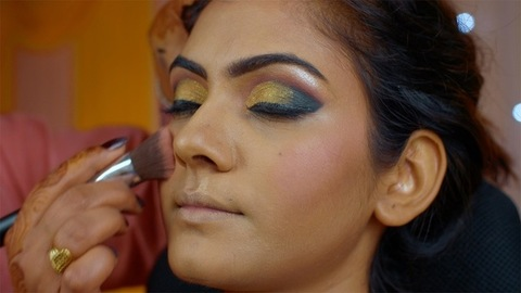 Indian bridal makeup - Beautician applying blush on a young Indian girl with a soft facial brush