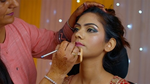 Makeup artist applying lip liner to the lips of a young woman - Indian beauty