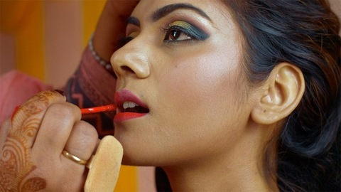 Makeup artist putting on lipstick with a soft lip brush - Indian bride makeup