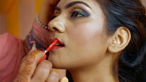 Indian beautician doing lip makeup of a young beautiful bride - makeup process