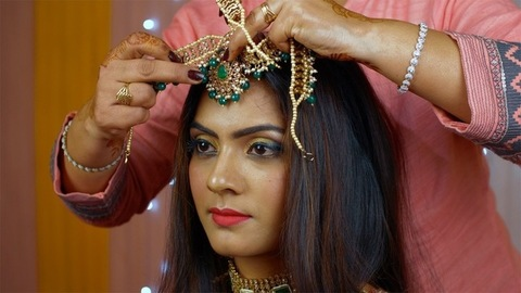 Female putting on heavy Maang Tika on a bride's forehead - Indian bridal makeup