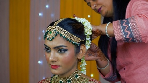 Indian mother putting Beli flower Gajra on her daughter hair bun - Indian bride