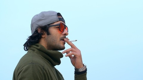 Charming young man wearing a cap and warm clothes smoking a cigarette