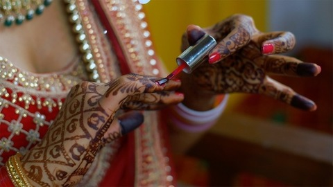 Attractive Indian bride with Henna decorated hands putting red nail paint