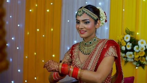 Punjabi bride putting on golden bridal bangles with Chuda in Henna decorated hands
