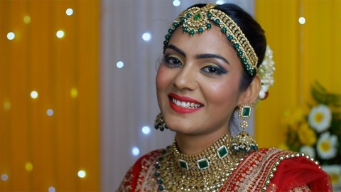 Young Indian bride smiling - Putting on beautiful earrings for her wedding function