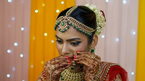 Beautiful Indian bride putting on a nose ring - bridal makeup in Indian wedding