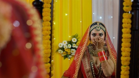 Lovely Punjabi bride putting on Bindi while looking in the mirror - bridal look
