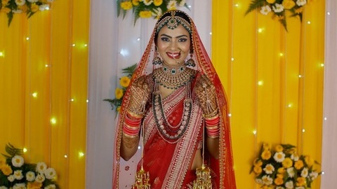 Pretty Indian bride holding her Ghoonghat/veil posing in her marriage ceremony