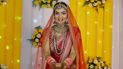 Newlywed north Indian bride standing with a box of vermilion/Sindoor on stage