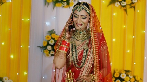 Smiling Indian bride dressed in traditional outfit and jewelry talking on a smartphone