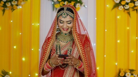 Indian bride typing on her mobile on a floral-decorated stage - Hindu marriage
