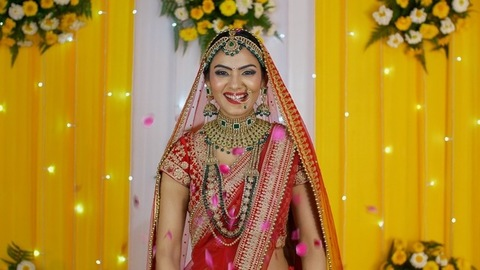 Traditional north Indian bride smiling and throwing flower petals - Hindu wedding