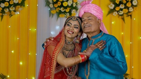 Attractive bride happily standing on the stage with her father - Indian wedding